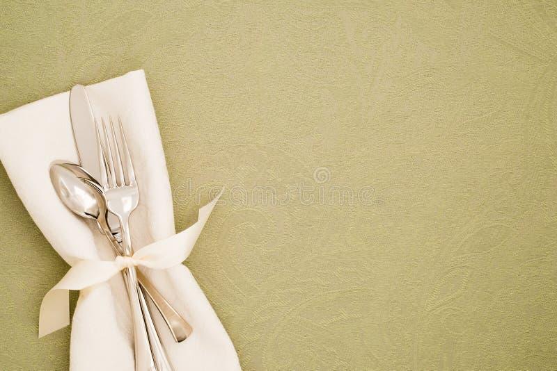 Definição do Local da Mesa com Silverware e guardanapo de pano branco em Tablecloth de Brocade Verde Claro como fundo com cópia s fotografia de stock royalty free