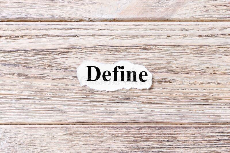 DEFINIERA av ordet på papper Begrepp Ord av DEFINE på en träbakgrund royaltyfri fotografi