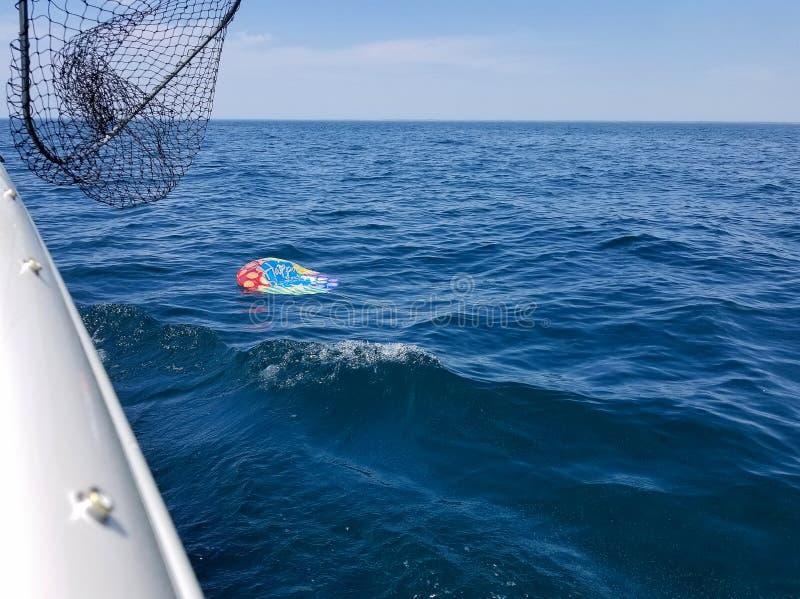 Deflaterad heliumballong som svävar i sjön royaltyfria foton