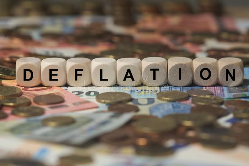 Deflation - cube with letters, money sector terms - sign with wooden cubes. Series of cube with letters from money sector royalty free stock photo