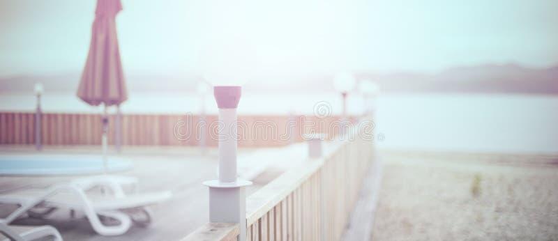 Defocus横幅木甲板海滩海海洋手段太阳懒人伞旅馆水池天空日出 库存照片