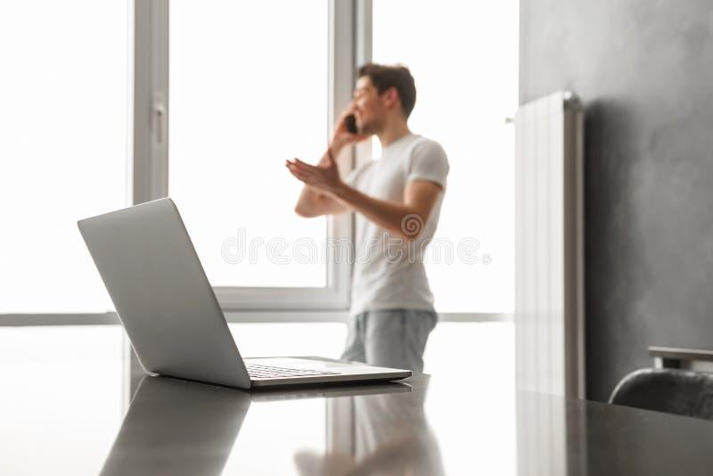 defocus的白种人人谈话在手机和使用膝上型计算机的 免版税库存照片