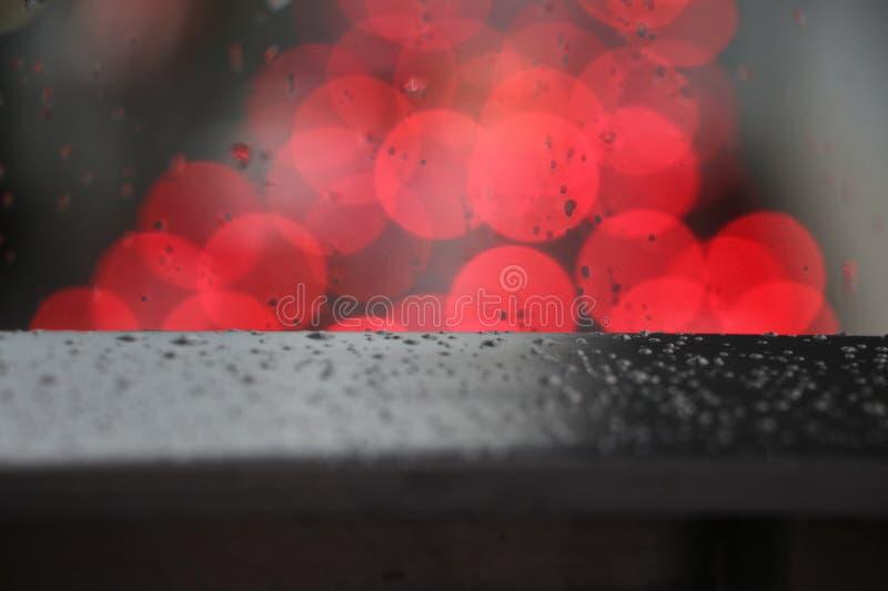Defocus czerwone światło zamazywał tło na nawierzchniowym szkle z deszczem fotografia royalty free