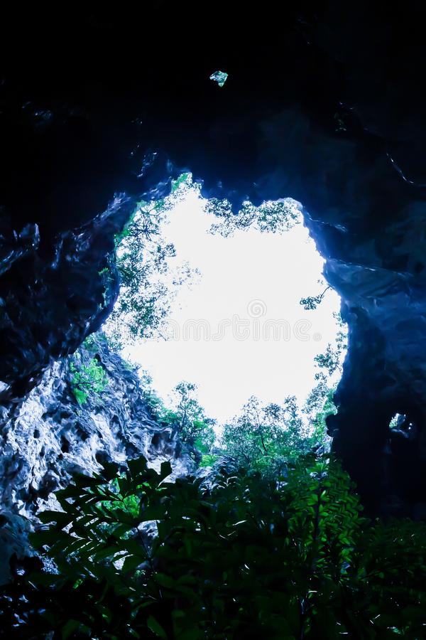 Defocus, foco macio Ideia inferior da entrada antiga misteriosa da caverna com plantas tropicais e o céu branco imagem de stock royalty free