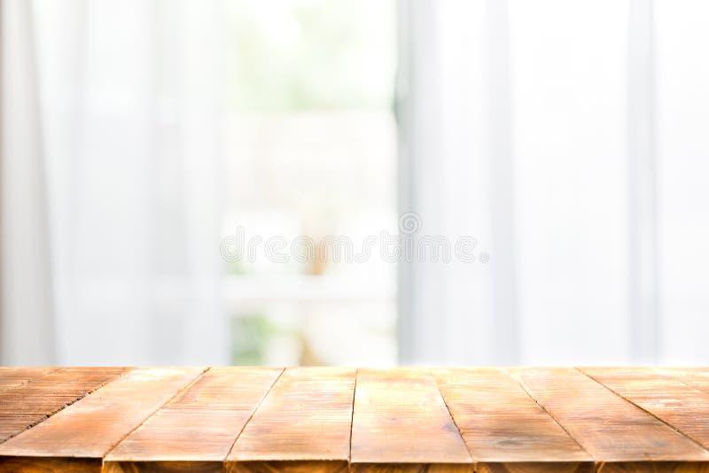 Defocused帷幕窗口和倒空与温暖的阳光的木台式 免版税库存照片