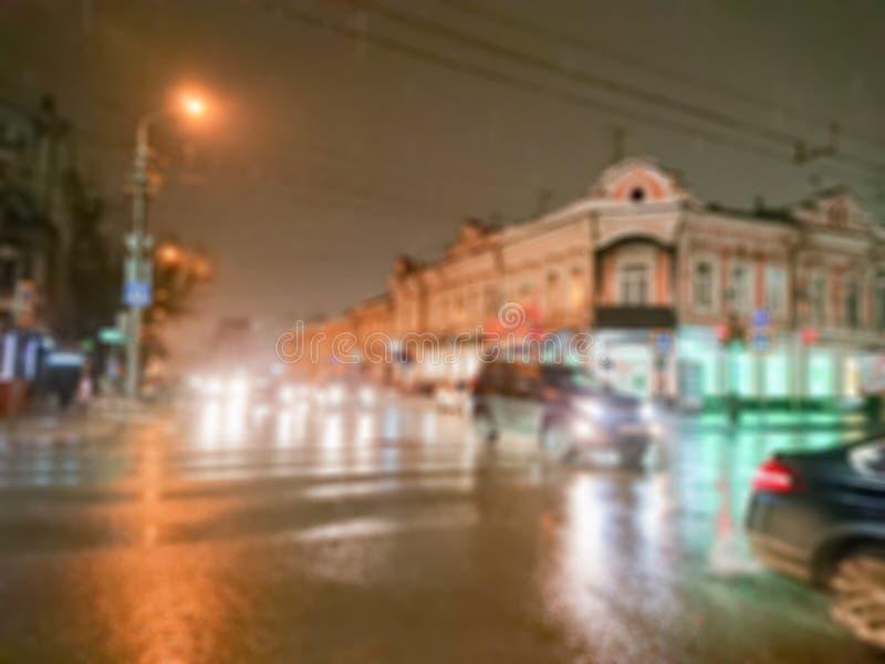 Defocused抽象图象 Bokeh作用 被弄脏的背景 在多雨天气的都市风景 汽车和夜光 免版税库存图片