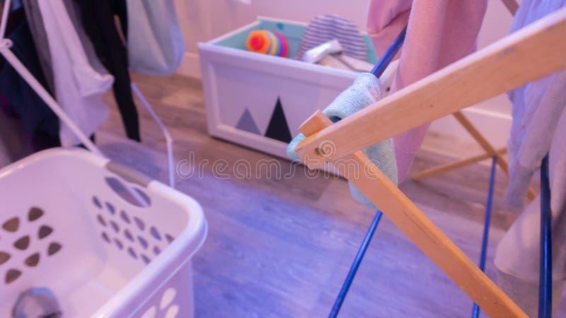Defocused洗衣店场面在室内客厅,有在烘干机架、洗衣篮和玩具箱的衣裳的 免版税库存图片