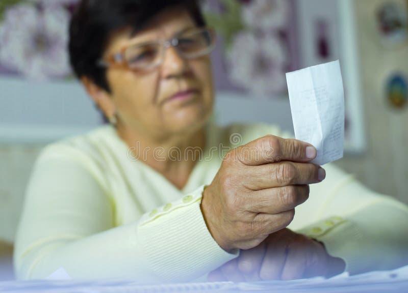 Defocused ältere alte Frau in den Brillen Kosten der täglichen Ausgaben zu Hause überprüfend lizenzfreies stockbild