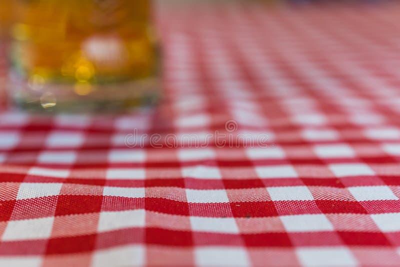 Defocused стекло пива на chequered скатерти стоковое фото
