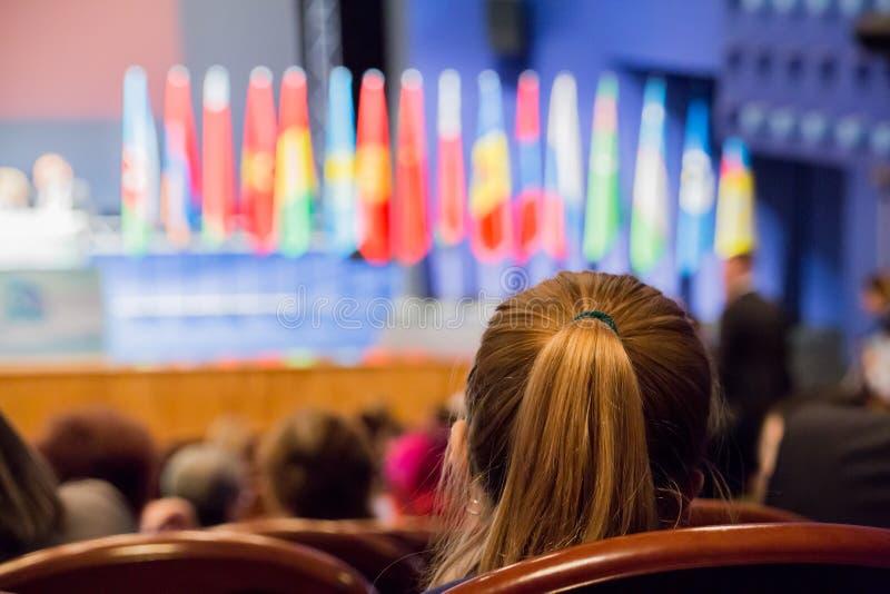 Defocused изображение Люди в аудитории Международная конференция Флаги различных стран на этапе стоковая фотография rf