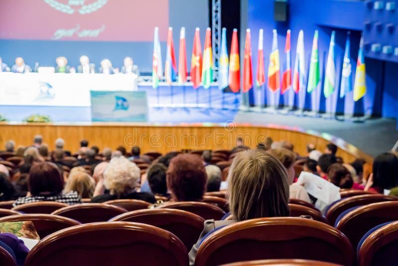 Defocused изображение Люди в аудитории Международная конференция Флаги различных стран на этапе стоковое фото rf