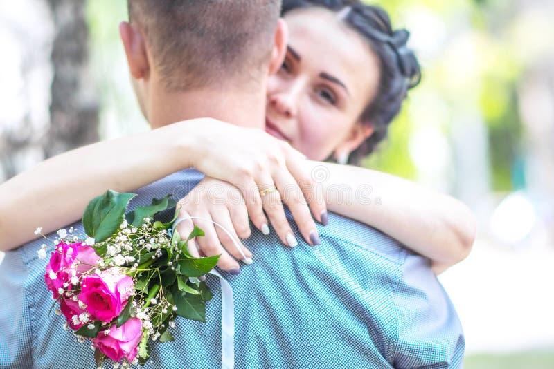 Defocused портрет красивой молодой женской невесты при малый букет роз цветка пинка свадьбы нежно обнимая шею a жениха стоковая фотография rf