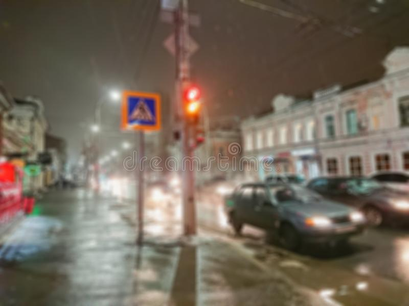 Defocused abstract image. Bokeh effect. Blurred background. Evening cityscape in rainy weather. Cars and night lights. City of Saratov, Russia stock image