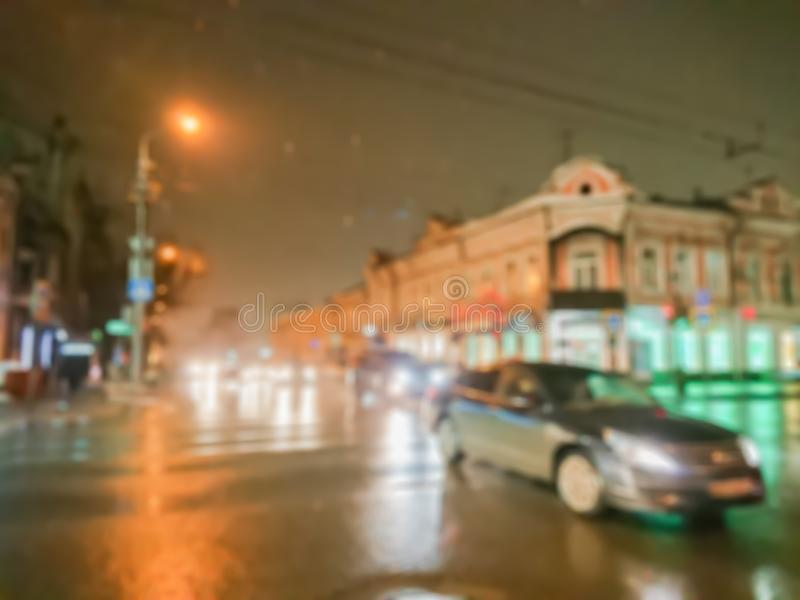 Defocused abstract image. Bokeh effect. Blurred background. Evening cityscape in rainy weather. Cars and night lights. City of Saratov, Russia stock images