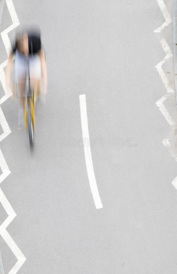 Defocused abstract  motion blur of young man riding a bike on bicycle lane stock photography