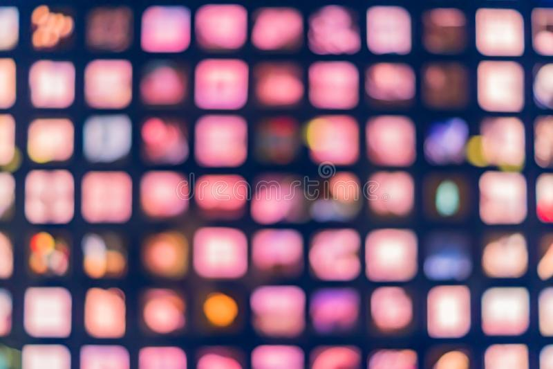Defocused abstract multicolored bokeh lights background. Square windows at night stock image