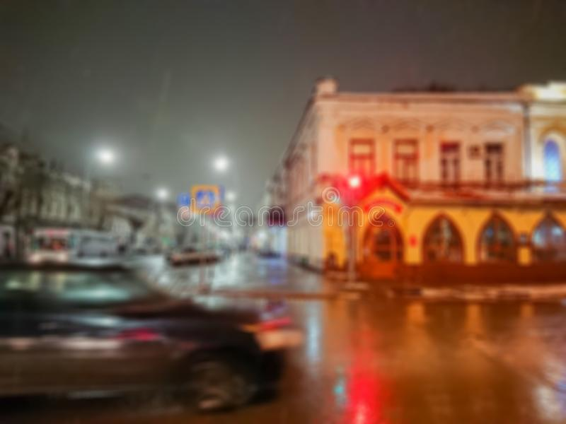 Defocused abstrakt bild Bokeh verkställer suddighet bakgrund Aftoncityscape i regnigt väder Bilar och nattljus royaltyfri bild