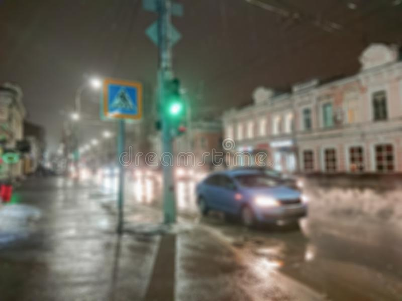 Defocused abstrakt bild Bokeh verkställer suddighet bakgrund Aftoncityscape i regnigt väder Bilar och nattljus fotografering för bildbyråer