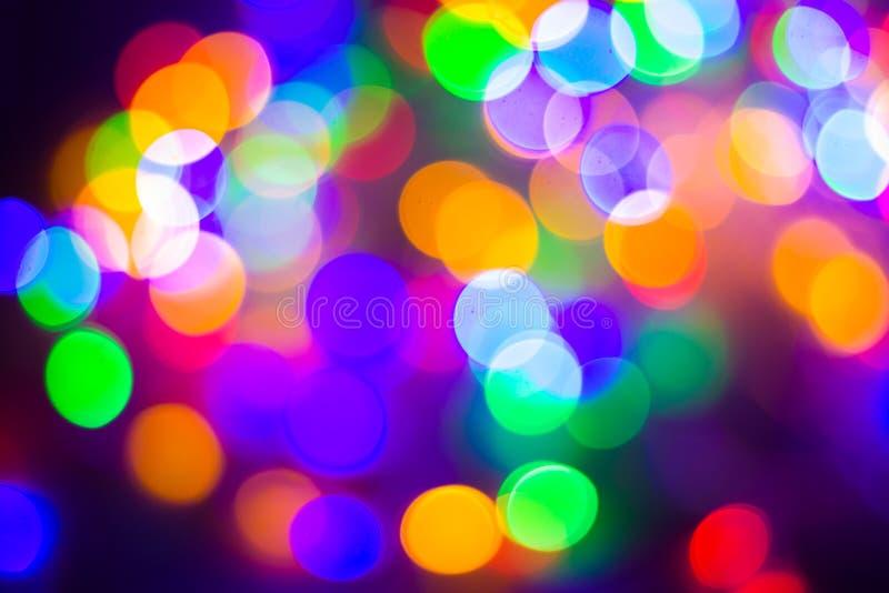 Defocused abstrakt mångfärgad bokeh tänder bakgrund Blått lilor, gräsplan, apelsin färgar - jul och begrepp för nytt år arkivfoton