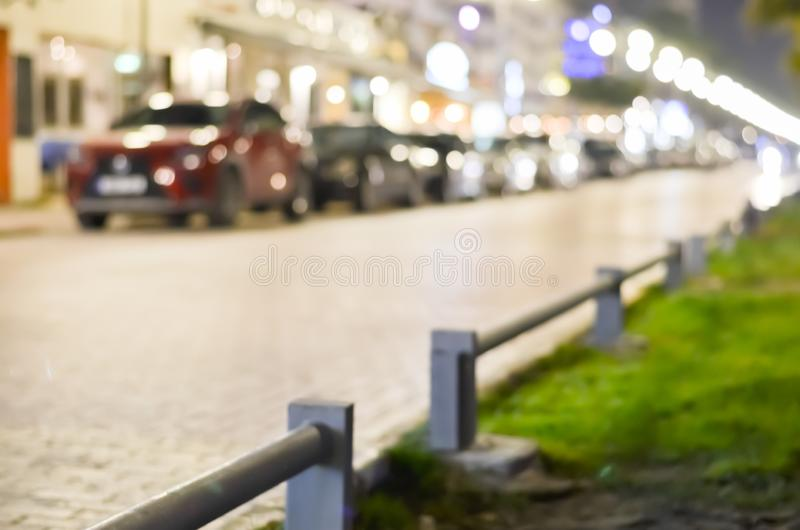 Blurred  background with cars parked in the street at night with lit street lights. Defocused background with cars parked in the street at night with lit street stock images