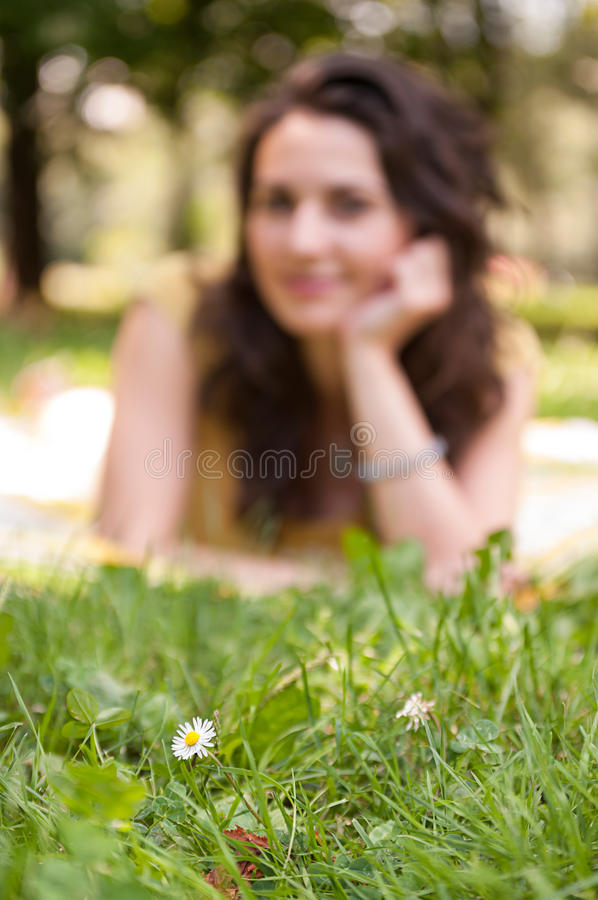 Defocused background with a young woman and a flower on focus at. Defocused background with a beautiful young woman and a tiny white flower on focus at royalty free stock photos