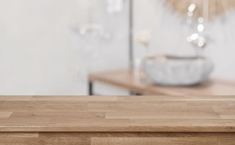 Defocused bathroom interior background with wooden table top in front royalty free stock image