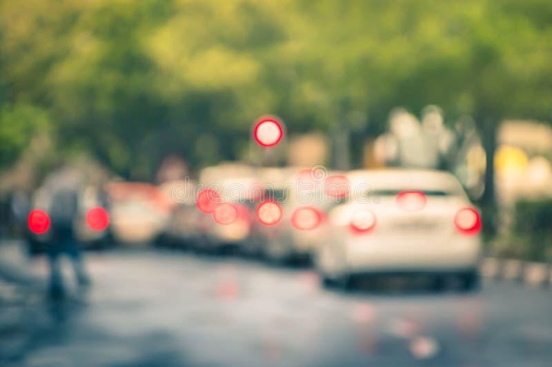 Defocused bilar i stadstrafikstockning i en regnig dag royaltyfria bilder