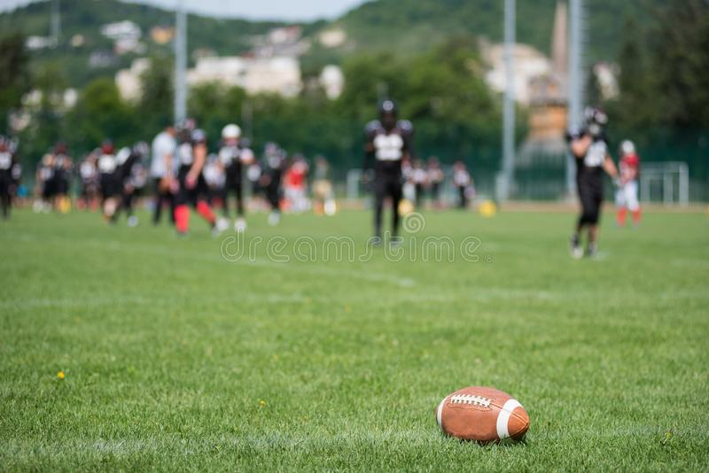 Blurred American football players. Defocused, blurred image of American football players and field. Ball in focus in the foreground stock photos