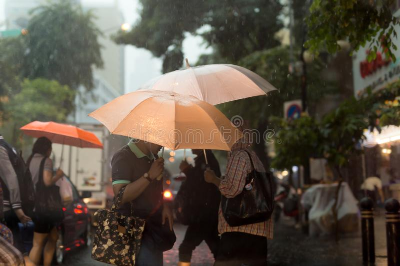 Defocused blurred people walking under the rain with umbrellas d royalty free stock image