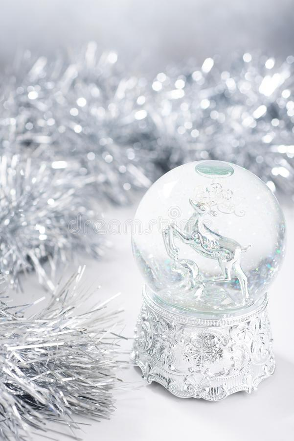 Defocused christmas background with silver christmas water globe and tinsel. Defocused background with silver christmas water globe and tinsel royalty free stock photography