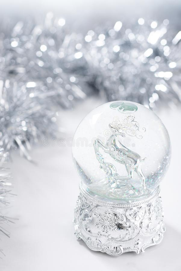 Defocused christmas background with silver christmas water globe and tinsel. Defocused background with silver christmas water globe and tinsel stock images