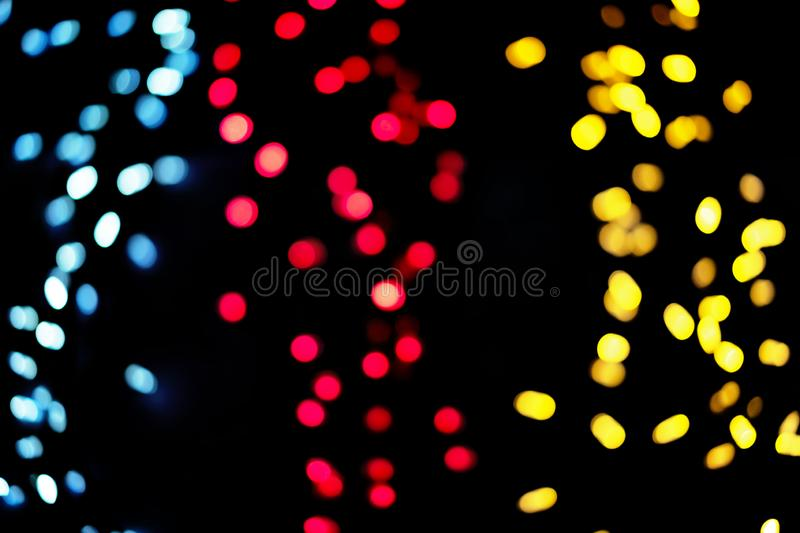 Defocused christmas garlands with colorful glow. Christmas background with multicolored bokeh royalty free stock images