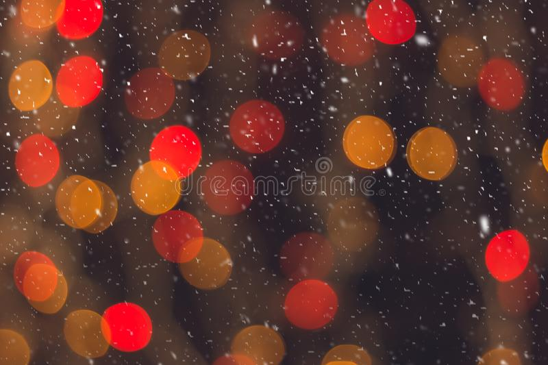 Defocused colorful lights of Christmas tree. Multicolored bokeh during snowfall. Background for greeting card. Winter composition. royalty free stock photo