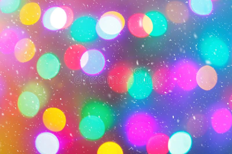 Defocused colorful ligths of Christmas tree. Multicolored bokeh lights during a snowfall. Background for greeting card. royalty free stock image