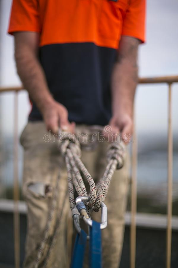 Defocused de l'inspecteur d'accès de corde inspectant la bride bleue de bandes calée avec fermer à clef les karabiners et l'agraf photo libre de droits