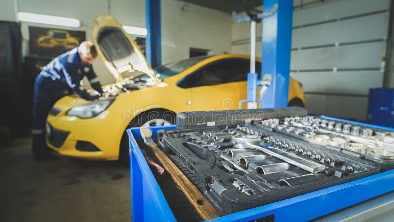 Defocused - en arbetarmekaniker kontrollerar det elektriskt i huven av den gula bilen, garageseminarium arkivfoton