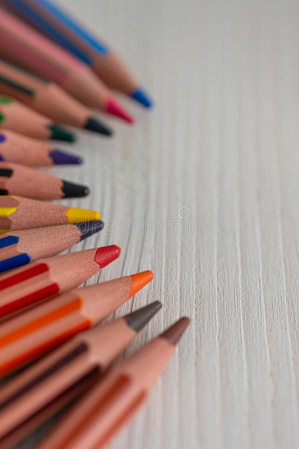 Defocused foreground, focused center and unfocused background of several colored pencils for school, in semicircle. On white wood in horizontal stock images