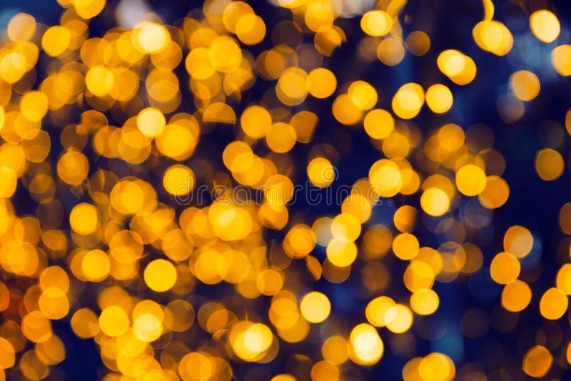 Abstract defocused glittering background. Blurry bokeh of night golden lights. stock photos
