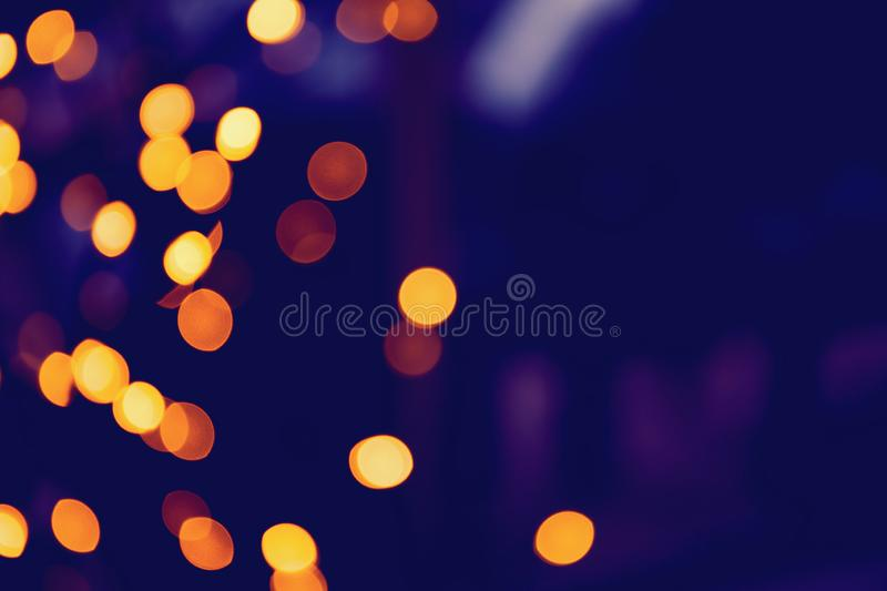 Defocused glittering background of golden garland christmas lights. Abstract blurry bokeh backdrop stock photos
