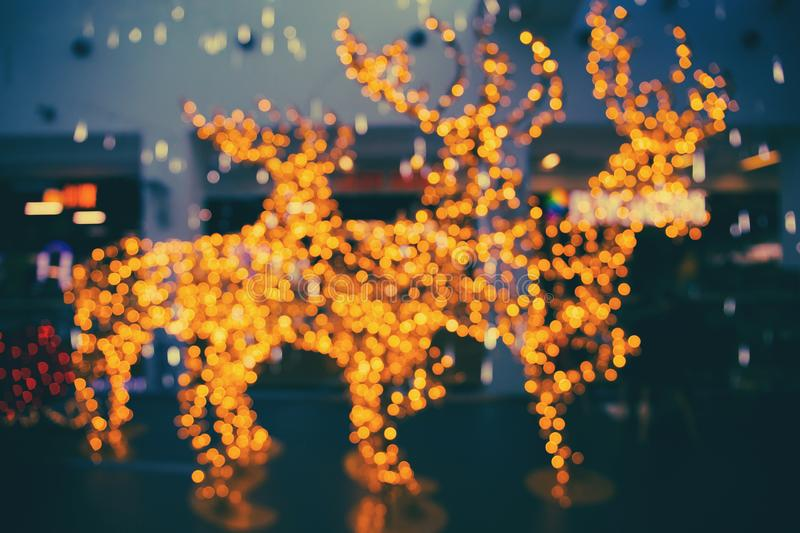 Defocused glittering background of golden garland christmas lights in the shape of a reindeer stock photography