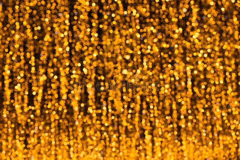 Defocused glittering background of golden garland  lights. Abstract blurry bokeh backdrop royalty free stock photography