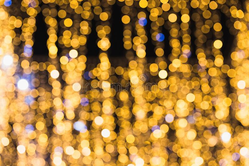 Defocused glittering background of golden garland  lights. Abstract blurry bokeh backdrop stock photography