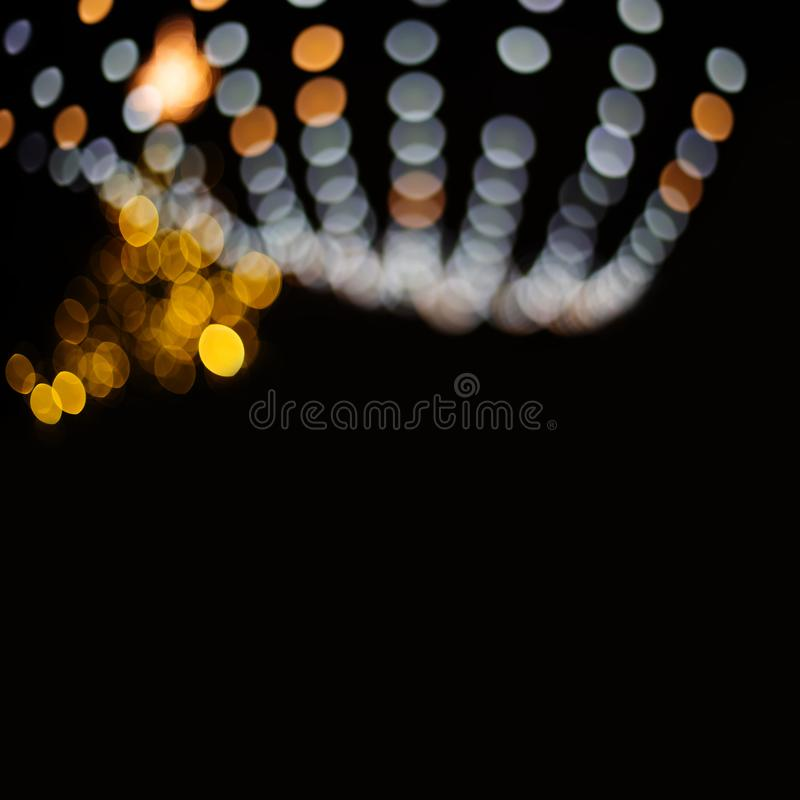 Defocused glowing light bulbs and bokeh effect. Golden gray magiacal pattern on a dark background. Abstract glitter. Lights on black, copy space stock photo