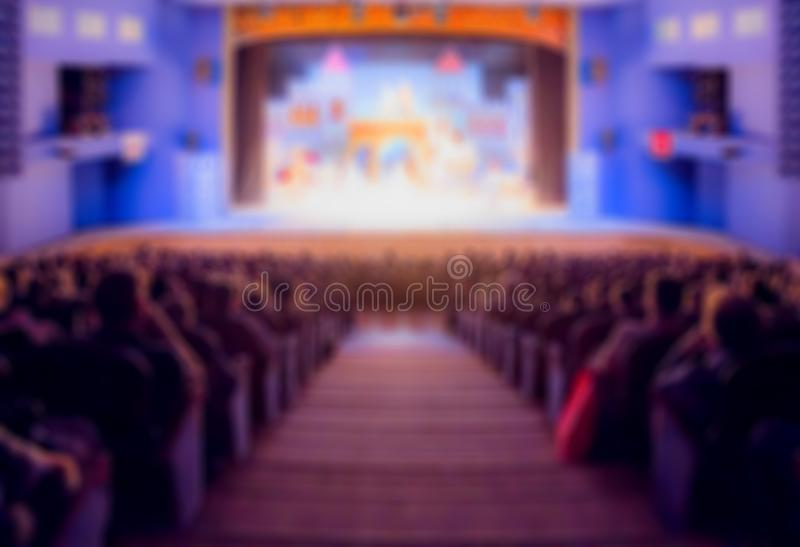 Defocused image. Auditorium in the theater during the performance. The scenery on the stage. Adults and children.  royalty free stock photo