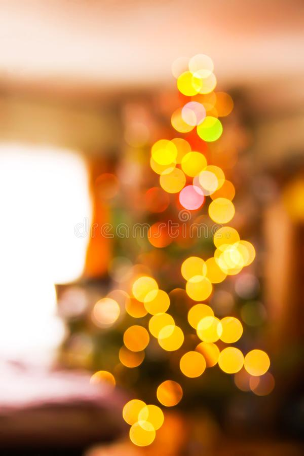 Defocused ligths of decorated Christmas tree in the rural house interior. Blurred New year festive background. Defocused bright ligths of decorated Christmas royalty free stock photos