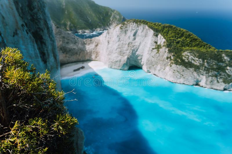 Defocused Navagio beach with green vegetation in foreground. Famous landscape of Zakinthos island, Greece, retro vintage. Toned royalty free stock image