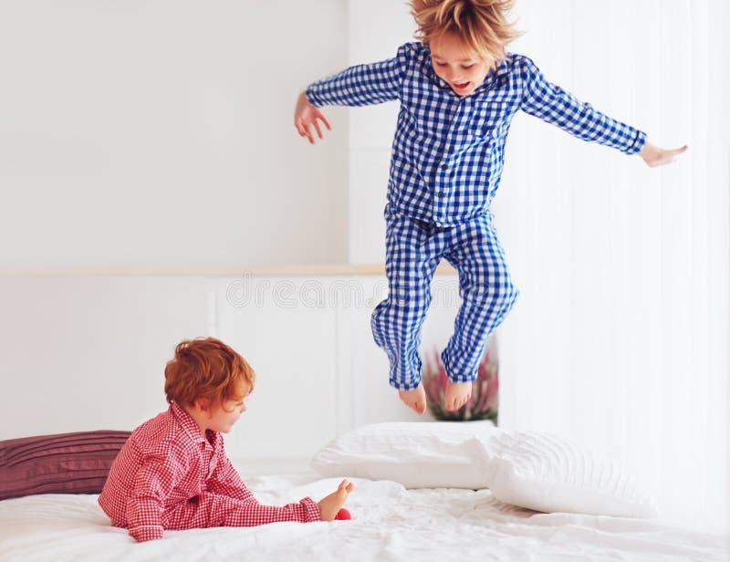 defocused opgewekte jonge geitjes, broers die in slaapkamer spelen, die op bed in pyjama's springen stock afbeelding