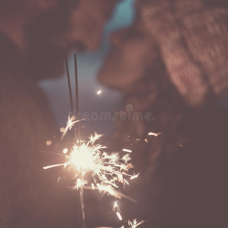 Defocused people together in love with fire light sparklers in foreground - concept of romantic relationship with man and woman. Defocused people together in royalty free stock photography
