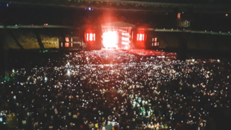 Defocused photo of big stadium full of fans on the rock music concert. Perfect backdrop for illustrating party, disco or stock photos