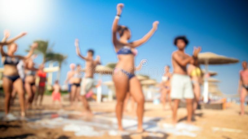 Defocused image of happy people dancing together on beach. Friends having soap foam sea beach disco party. royalty free stock photography